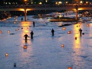 灯籠が途中で止まらないように川で交通整理をしている人がいるんです。