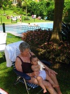 プールサイドで。おばあちゃまの膝の上で小休止。
