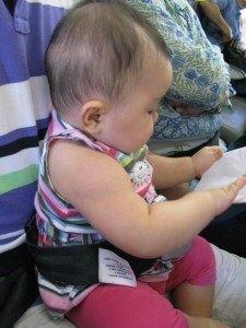夫の膝の上でシートベルトを装着している娘。