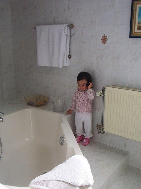 義母と一緒に遊びながら、お風呂場で電話をかけるふりをする娘。