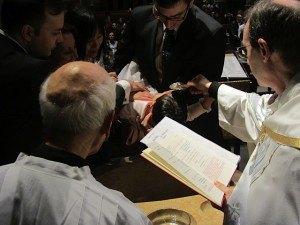 夫が娘をしっかりかかえて横にします。司祭が帆立貝の形をした銀のお皿で聖水を頭にかけます。
