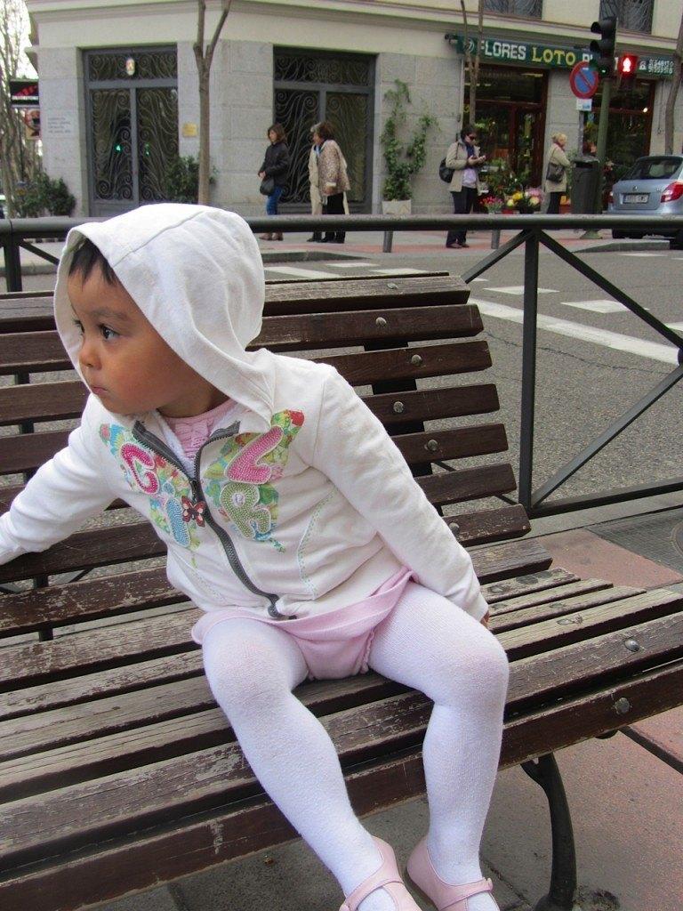 「お買い物」の途中でベンチで休む娘。後ろはいつも訪ねるお花屋さん。