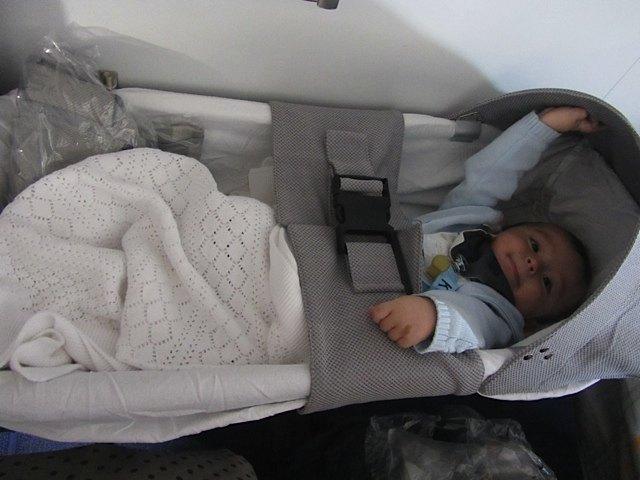 機内での健斗。こういう赤ちゃんベッドが付く席を予約しました。