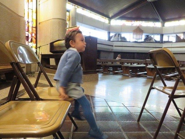 洗礼式の最中に椅子に上ったり降りたりしている息子。