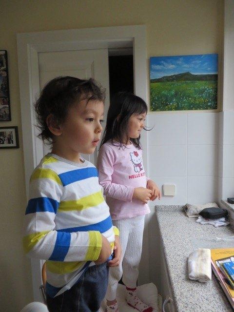 台所の窓の外に見えるショベルカーに興味津々の子供達。